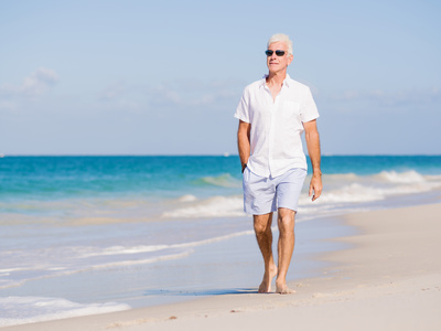 Man in white clothes on the beach on sunny day